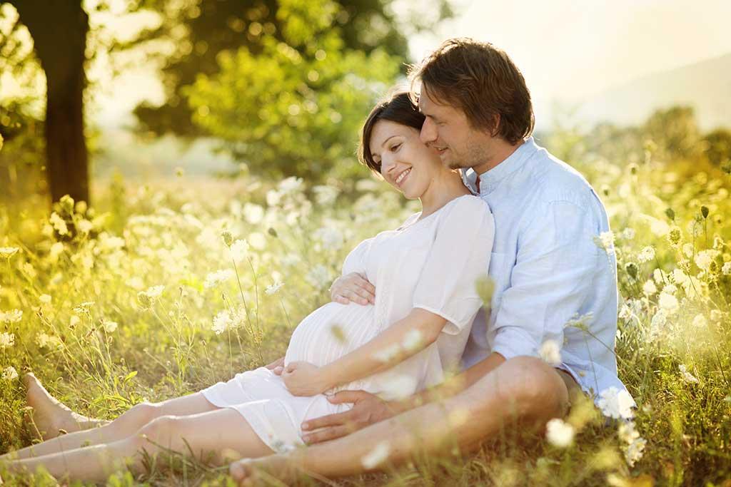 Sittende gravid kvinne i sommereng